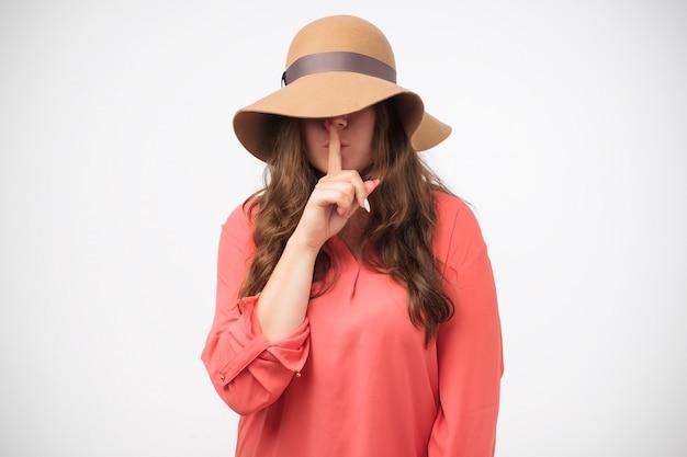 Misteriosa chica en señal de silencio de gesto de sombrero sosteniendo el dedo índice en los labios