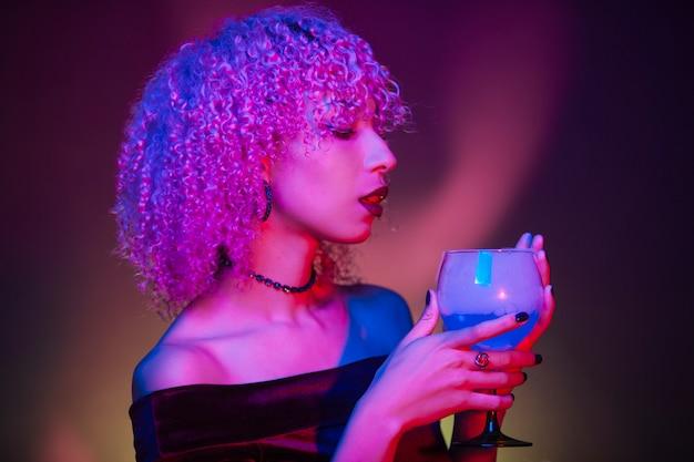 Misteriosa mujer afro sosteniendo una bebida nocturna en halloween