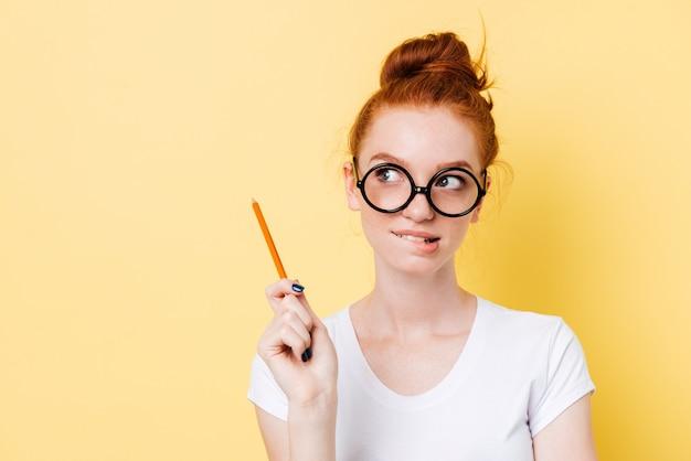 Misteriosa mujer de jengibre con anteojos muerde su labio con lápiz
