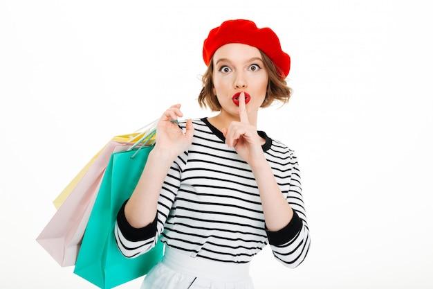 Misteriosa mujer de jengibre sosteniendo paquetes y mostrando un gesto secreto mientras mira a la cámara Foto gratis