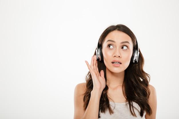 Misteriosa mujer morena en auriculares escuchando música y mirando a otro lado sobre gris