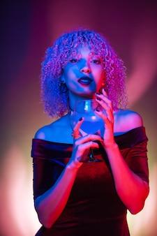 Misteriosa mujer negra en una discoteca con una bebida azul