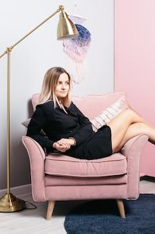 Misteriosa mujer pensativa en vestido negro en silla rosa