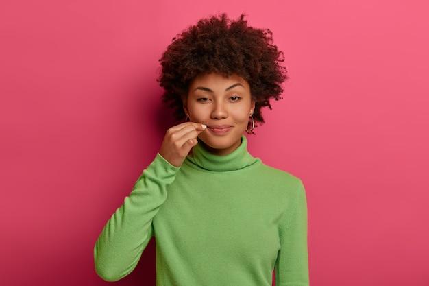 Misteriosa mujer rizada cierra la boca con cremallera, dice un secreto, cierra los labios con el candado, hace prometer que no le contará a nadie información confidencial, usa un jersey verde