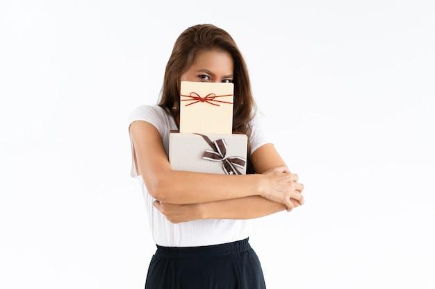 Misteriosa niña escondida cara detrás de cajas de regalo