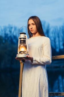 Misteriosa niña mística en un oscuro bosque nocturno con una lámpara de queroseno en sus manos