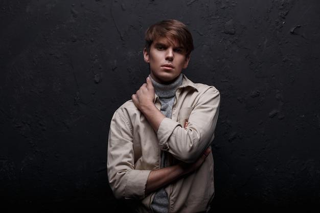 Misterioso joven serio con un corte de pelo a la moda en una chaqueta ligera con un suéter vintage en jeans azul está de pie y mirando a la cámara en el interior cerca de la pared negra. chico guapo europeo