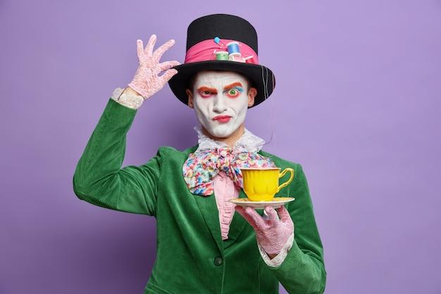 El misterioso personaje masculino serio del país de las maravillas frunce el ceño, mantiene la mano en el sombrero, bebe té en los vestidos de fiesta para halloween, finge ser un sombrerero loco, tiene maquillaje colorido aislado sobre una pared púrpura