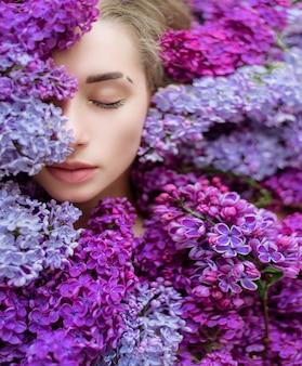 La mitad de la cara de la joven rubia caucásica con los ojos cerrados rodeada de un montón de lilas moradas y violetas, papel tapiz, melodía de primavera