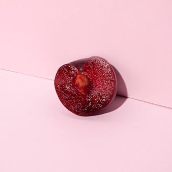 Mitad cereza sobre fondo rosa