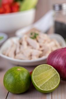 La mitad corta limones y cebollas rojas colocadas sobre una mesa de madera.