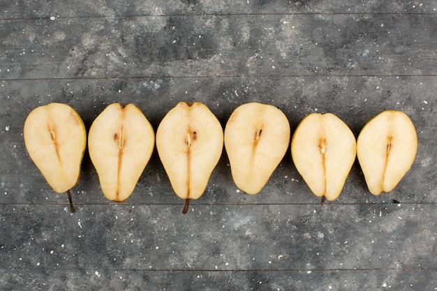 La mitad corta peras maduras forradas sobre un escritorio gris
