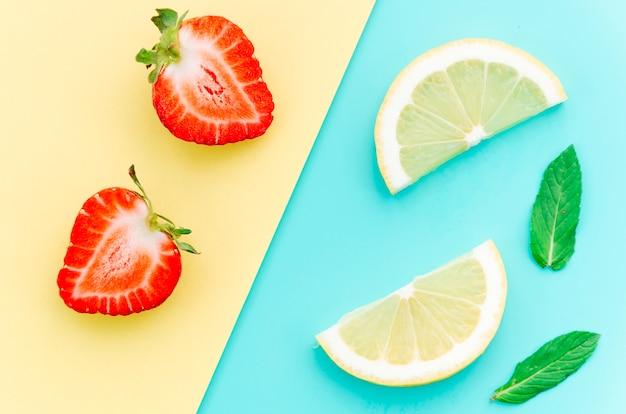 La mitad de fresas y rodajas de limón en la mesa