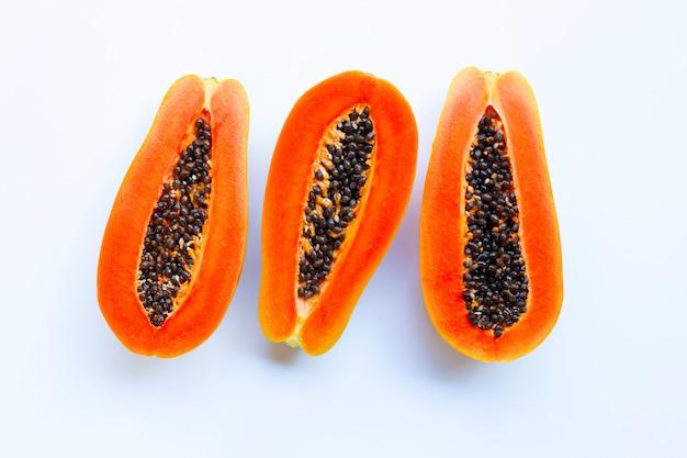 La mitad de la fruta de papaya madura con semillas aisladas sobre fondo blanco