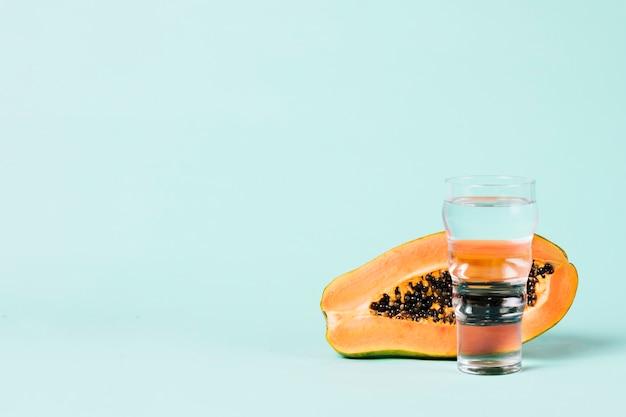 La mitad de fruta de papaya y vaso de agua