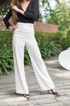 La mitad inferior del cabello largo piernas femeninas jóvenes en el estilo de moda con tacón alto, tomar fotos al aire libre en el jardín.