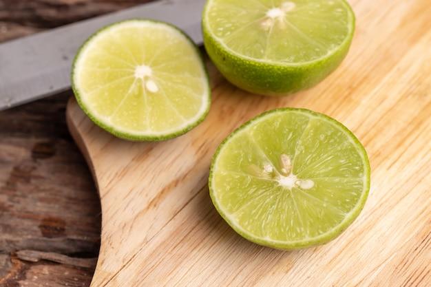 La mitad de la lima verde y la semilla con un cuchillo colocan en una tabla de madera