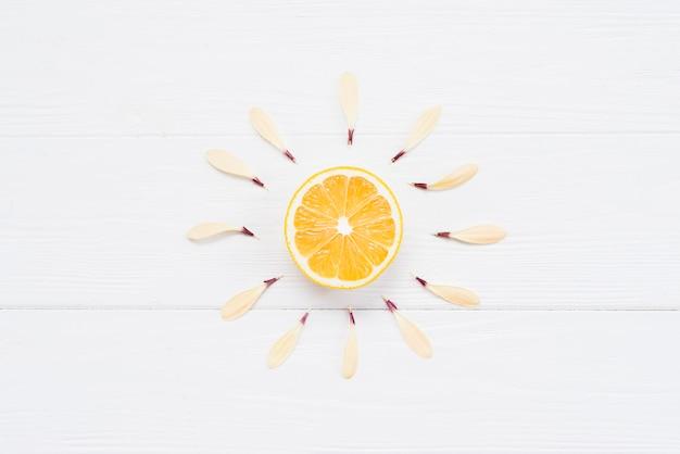 La mitad de limón con pétalos sobre fondo blanco