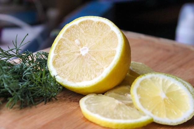 Mitad de limón y rodajas sobre fondo de tablero de madera con eneldo