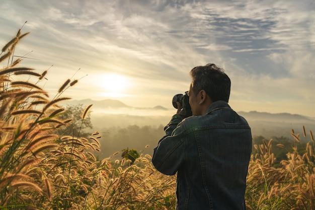 La mitad de la longitud de un hombre caucásico tomando una foto de una montaña brumosa en el momento de la salida del sol