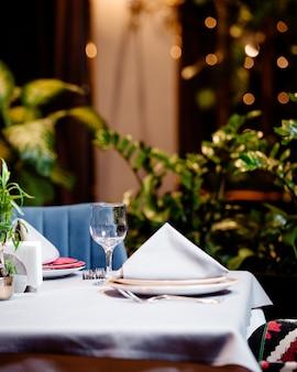 La mitad de la mesa de restaurante vacía con plato de cristal y cubiertos.