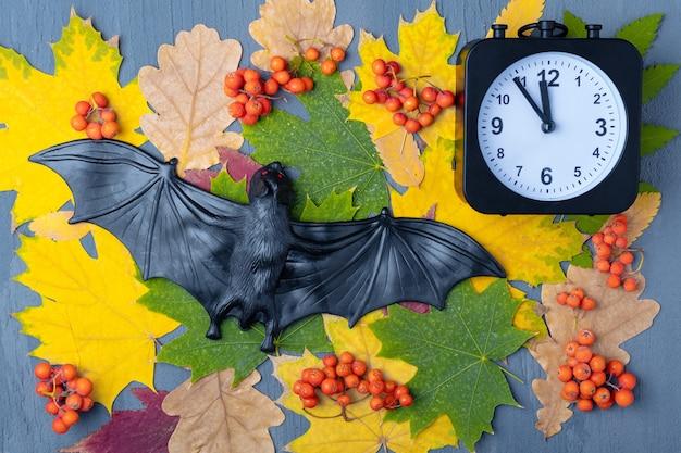 En mitad de la noche de halloween. murciélago negro de halloween y reloj sobre un fondo de hojas coloridas y bayas naranjas. feliz tarjeta de halloween. es hora de celebrar halloween