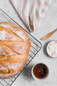 La mitad de pan blanco redondo y una taza de té plano