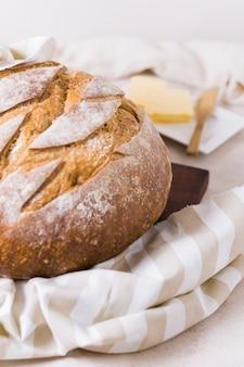 La mitad de pan redondo sobre tela y mantequilla borrosa