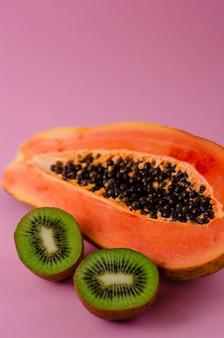 La mitad de papaya fresca madura y kiwi en rosa