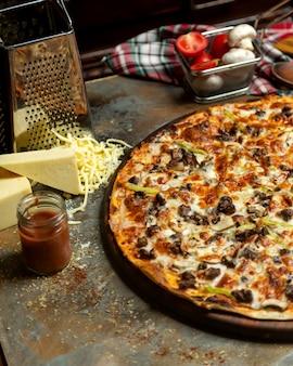La mitad de la pizza de carne con pimiento, tomate, champiñones y queso