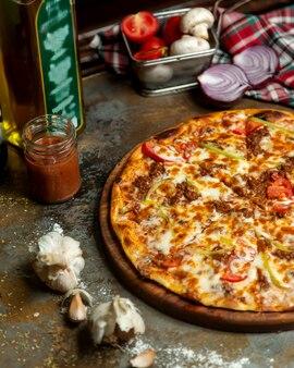 La mitad de la pizza de carne con pimientos de tomate y queso.