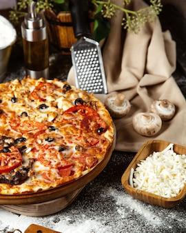 La mitad de la pizza mixta y la porción de queso rallado