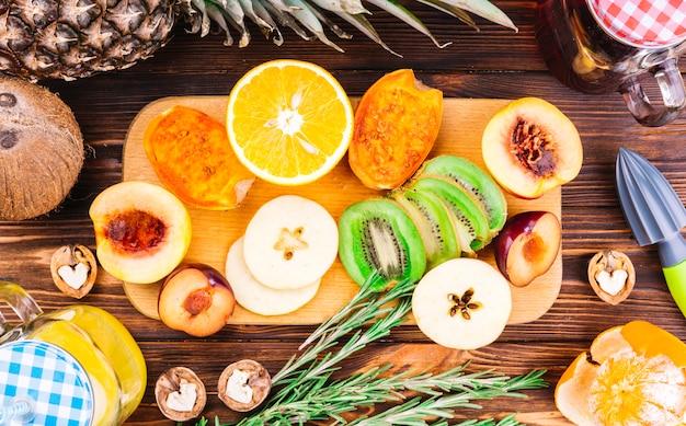 A la mitad rodajas de frutas frescas; nueces y romero en mesa de madera