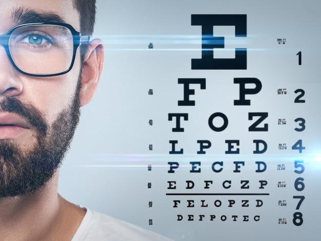 La mitad del rostro masculino y la tabla optométrica
