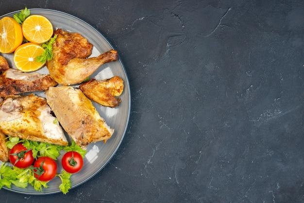 Mitad superior vista pollo al horno tomates frescos rodajas de limón