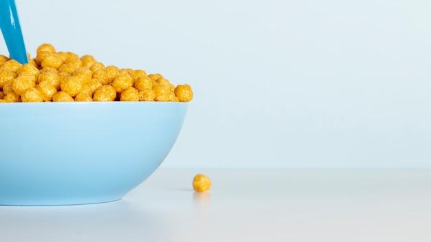 La mitad del tazón con cereales y copia espacio de fondo