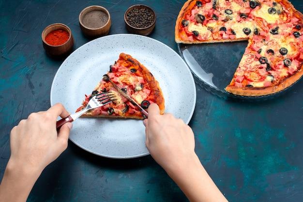 La mitad de la vista superior horneada deliciosa pizza con aceitunas, salchichas y queso hembra comiéndolo en el escritorio azul.