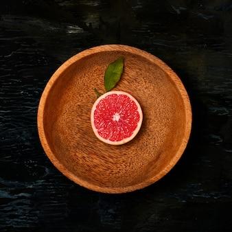 Mitades de cítricos de pomelo en placa de madera