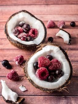 Mitades de coco con bayas congeladas sobre un fondo de madera oscuro