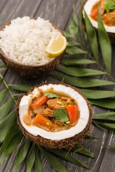 Mitades de coco rellenas de estofado y arroz.