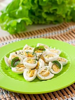 Mitades de huevos de codorniz cocidos en un plato verde