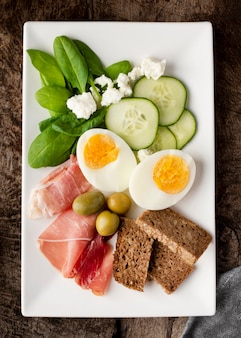Mitades de huevos y verduras en la placa blanca.