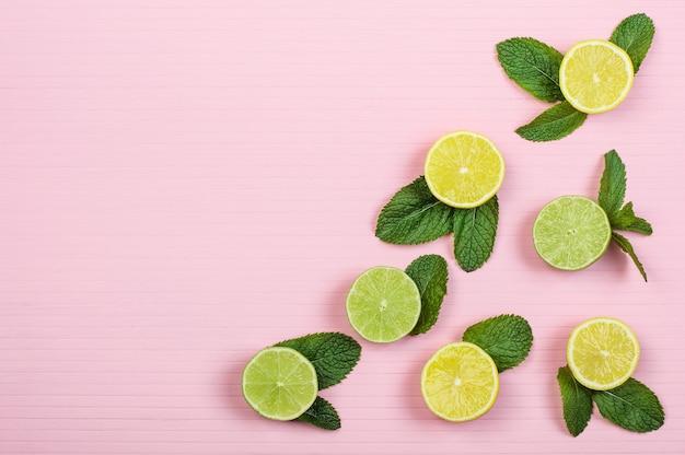 Mitades de limones y limas, menta sobre fondo de madera rosa, espacio de copia