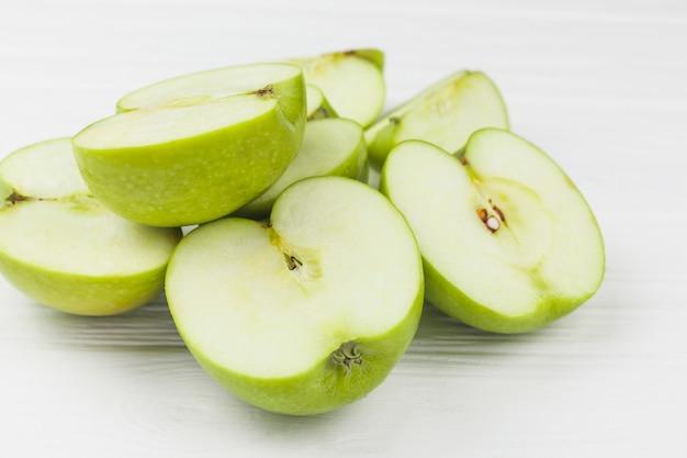 Mitades de manzanas jugosas en mesa blanca
