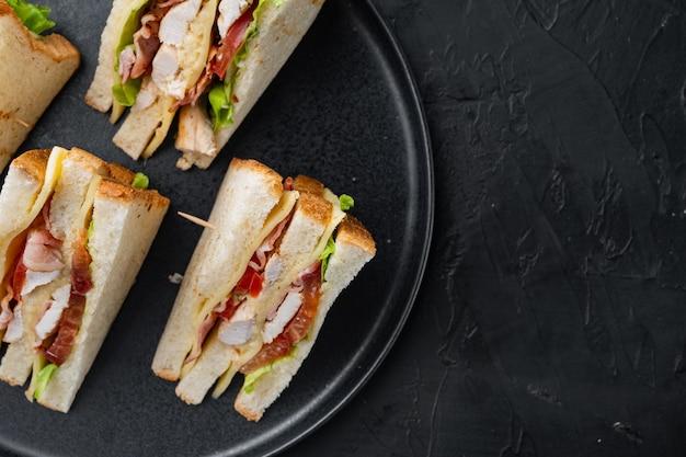 Mitades de sándwich de pollo casero, sobre mesa negra, vista superior