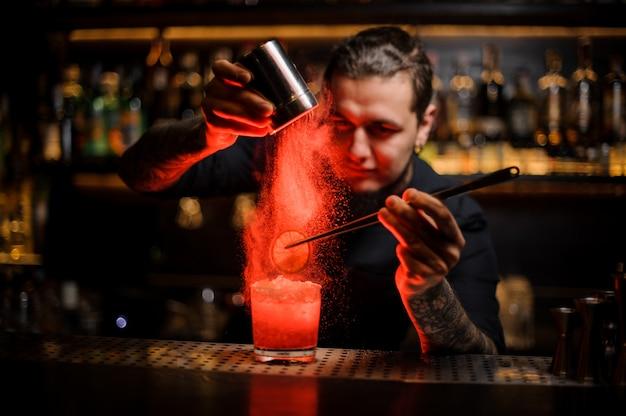 Mixólogo agregando especias en polvo en una copa de cóctel con una rodaja de limón
