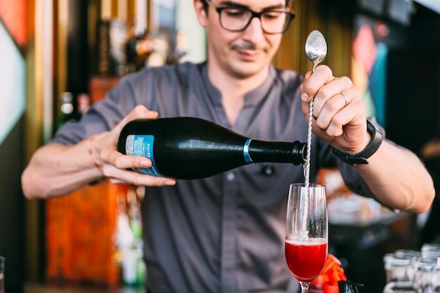 Mixólogo haciendo cóctel de refresco italiano rojo vertiendo vino con una cuchara larga en vaso.