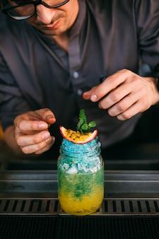 El mixólogo masculino está haciendo un cóctel azul y amarillo y decorando cuidadosamente con fruta de la pasión.
