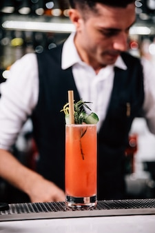 El mixólogo masculino está haciendo un cóctel rojo y decorando cuidadosamente con rodajas de pepino sobre una copa de cóctel en la barra de mostrador del restaurante.