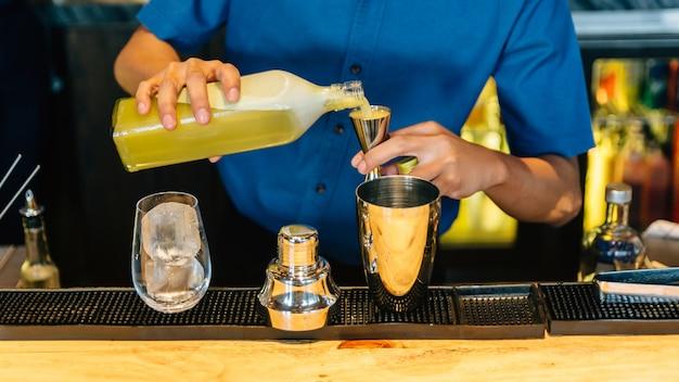 Mixólogo que hace cóctel yuzu con coctelera, jiggers de tamaño doble y vaso